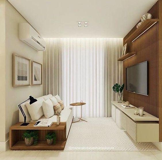 Sala de televisão com cortinas em duas cores neutras e painel de televisão amadeirado.