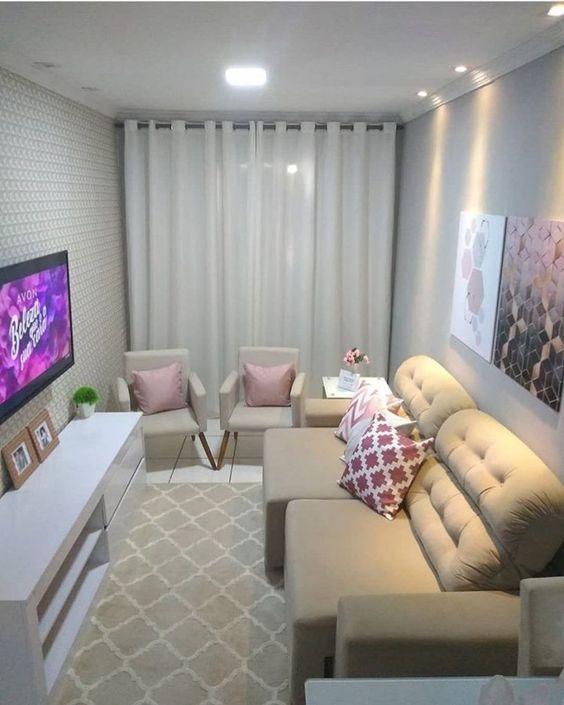 Sala decorada com duas poltronas, sofá e almofadas rosas.