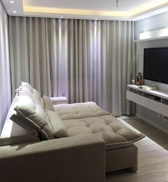 Decoração de apartamento pequeno com sala de cores neutras e painel de televisão.