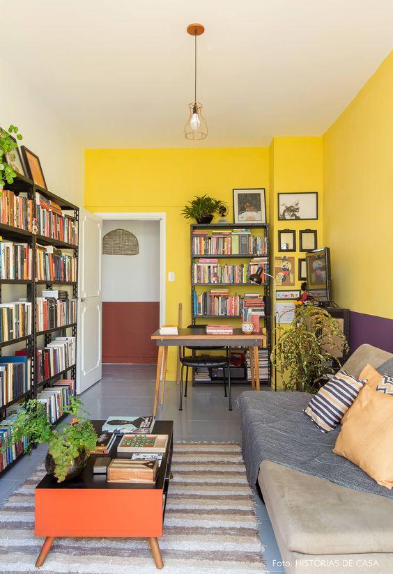 Sala de leitura decorada com vasos de plantas, quadros e livros.