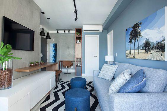 Sala decorada com sofá, almofadas, puffs, quadro e parede azuis.