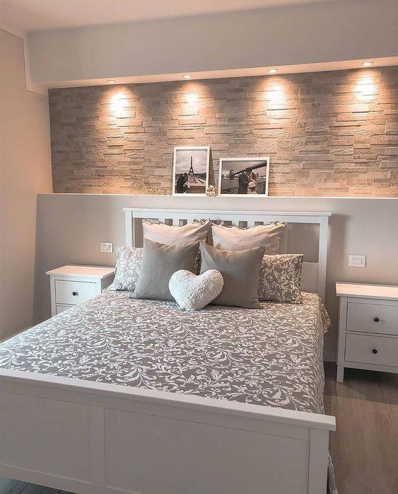 Decoração de apartamento pequeno  com almofadas e quadros com fotos em quarto de casal.