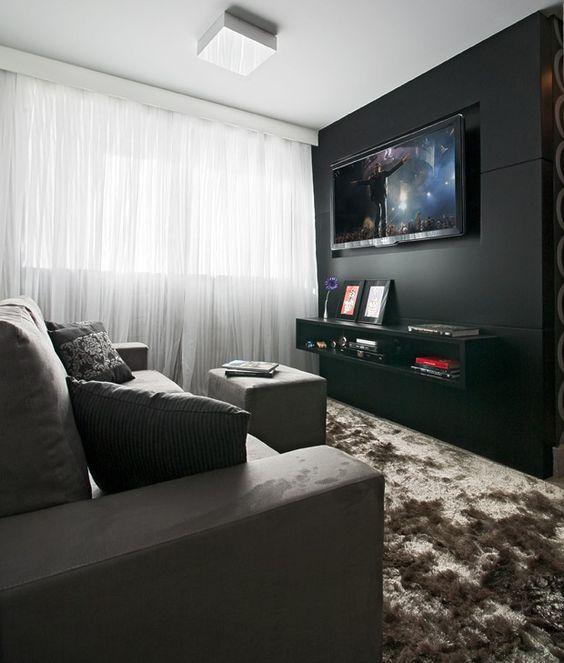 Sala decorada com cores escuras e cortina branca.
