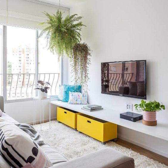 Decoração de sala de estar com vasos de plantas suspensos e um na prateleira.