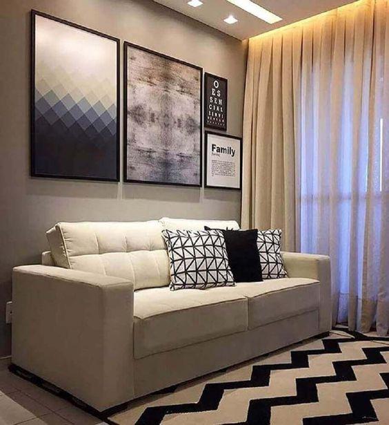 Sala pequena com almofadas e quadros decorativos.