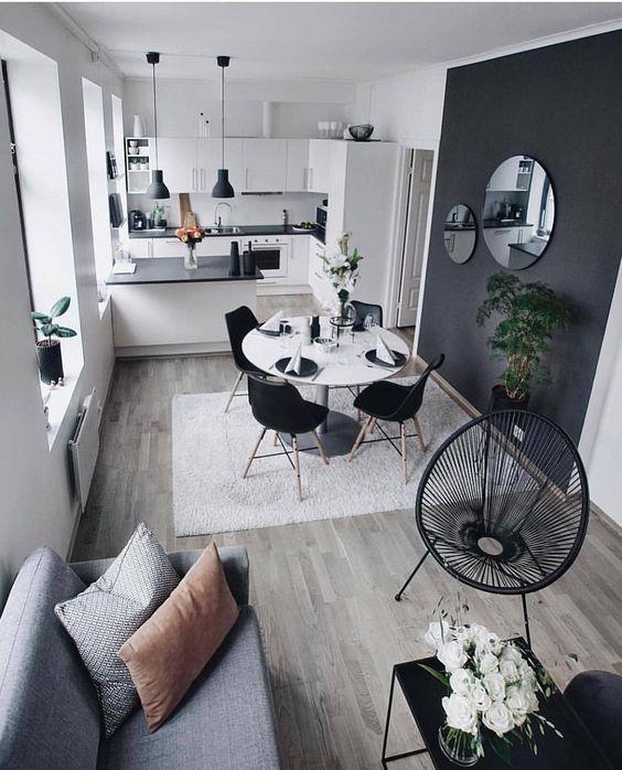 Apartamento pequeno com ambientes decorados em preto e branco.