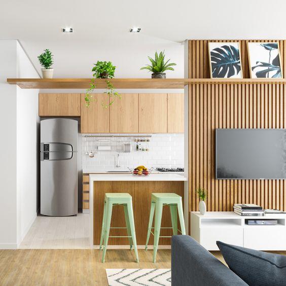 Cozinha integrada com sala por um balcão e banquetas verdes decorativas.
