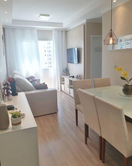 Decoração de apartamento pequeno com cores neutras e cortinas que cobrem a parede.