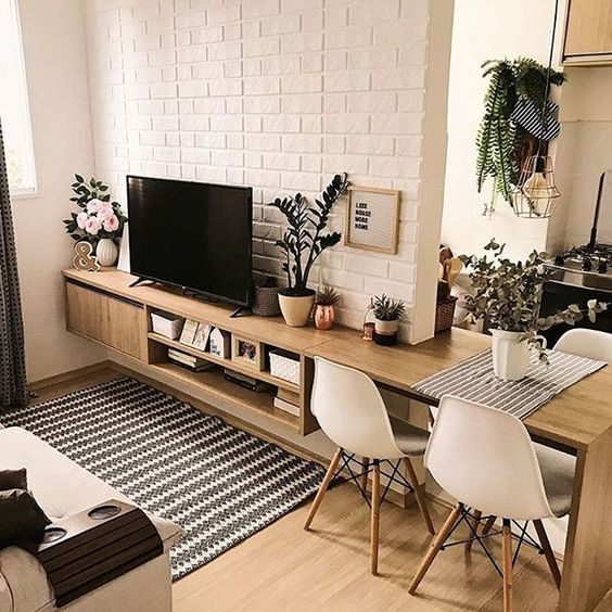 Hack de televisão integrado com mesa de jantar em ambiente decorado.