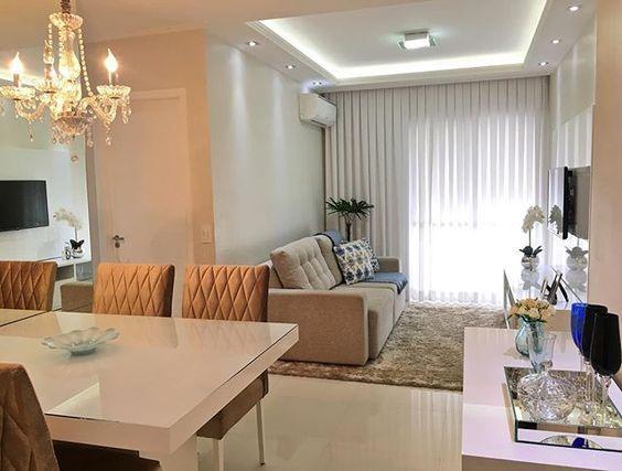 Sala de estar e de jantar com cores neutras, espelho grande e lustre decorativo.