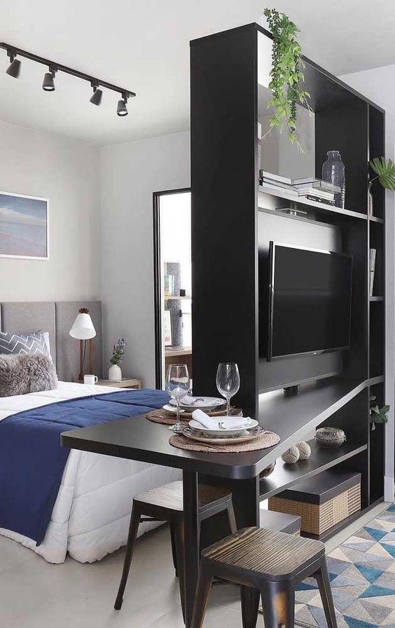 Quarto e sala divididos por um painel de televisão.