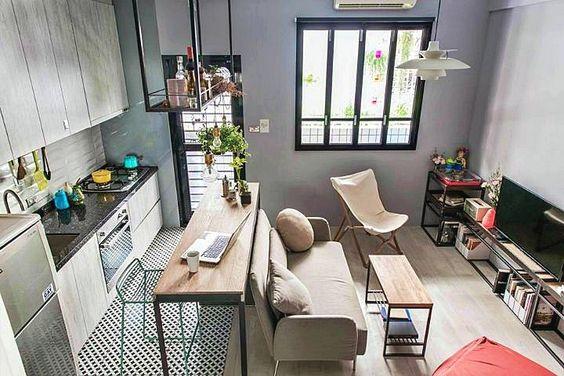 Apartamento com sala e cozinha divididos por um balcão e o sofá.