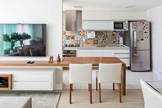 Decoração de apartamento pequeno com cozinha colorida e sala com cores neutras.