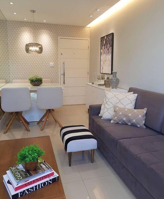 Decoração de apartamento pequeno com espelho grande, almofadas em cores neutras e pequeno vaso de planta.