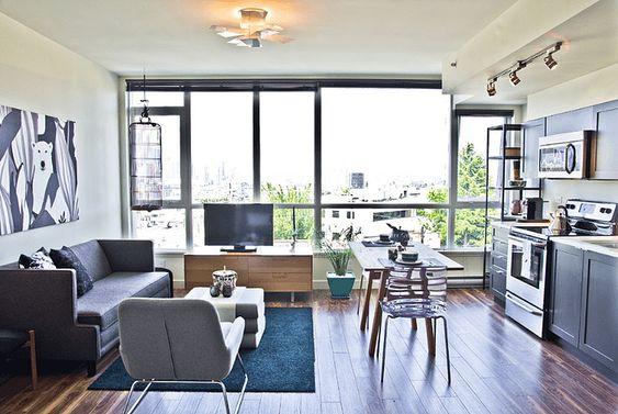 Apartamento com sala e cozinha integrados dividiso pela mesa.