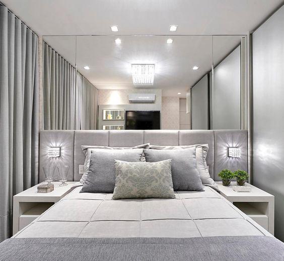 Decoração de apartamento pequeno com espelho grande em cima da cabeceira de cama de casal.