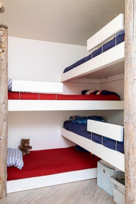 Quarto com quatro camas de solteiros cruzadas, uma em cima da outra.