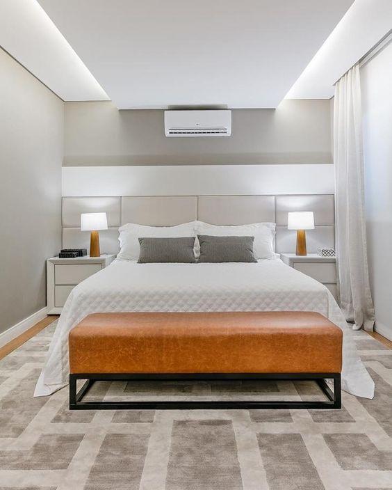 Quarto minimalista com cama de casal e mesinhas de cabeceira.