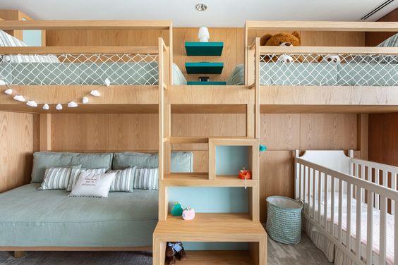 Decoração de quarto de hóspedes com três camas e um berço.