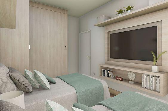 Decoração de quarto com televisão embutida em painel de madeira e quartos com móveis com cores neutras.
