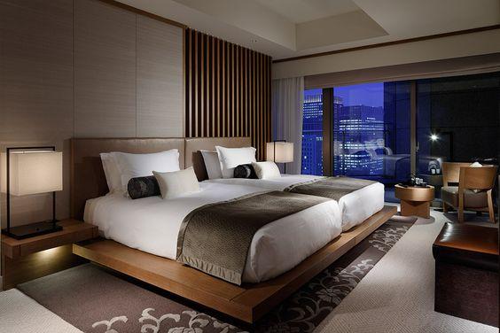 Decoração de quarto de hóspedes com uma estrutura única de madeira com dois colchões de solteiro.