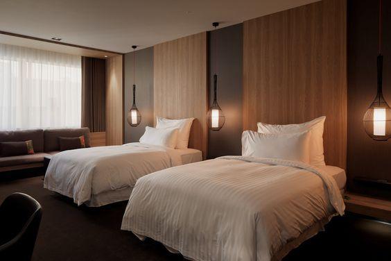 Quarto grande de hóspedes com duas camas, parede de madeira e luminárias ao lado das camas.