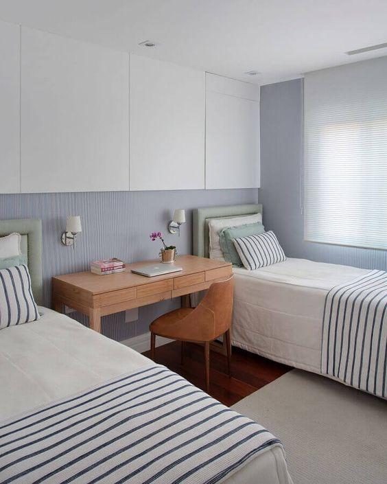 Decoração de quarto de hóspedes com duas cama de solteiro e uma mesa de madeira.
