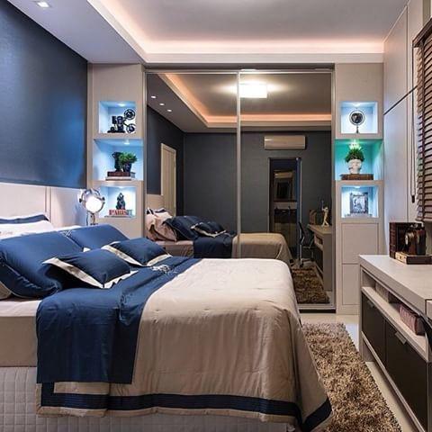 Nichos iluminados dos lados do guarda-roupa espelhado e roupa de cama de casal com detalhe azul.