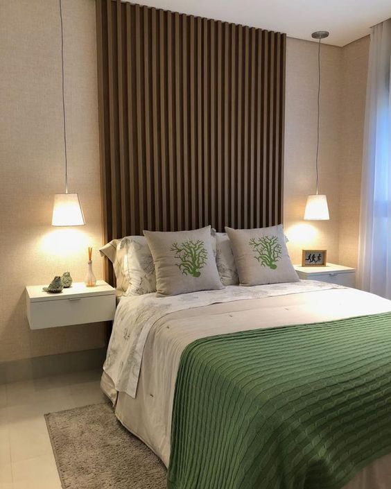 Decoração de quarto de casal com painel de madeira e roupa de cama com detalhes verdes.