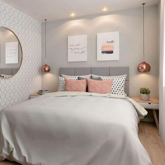 Quarto de casal com papel de parede, espelho redondo e duas mesinhas de cabeceira com iluminação suspensa.