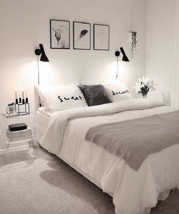 Quarto preto e branco minimalista com luminárias suspensas em cima da cama.