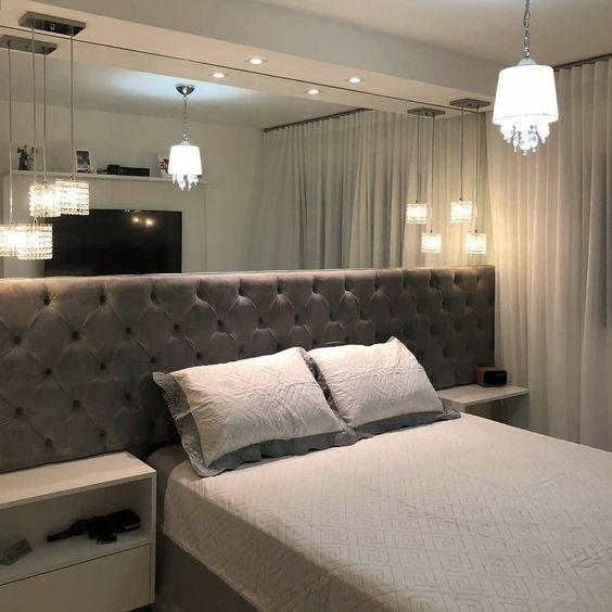 Cabeceira de cama de casal acolchoada e um espelho que vai de fora a fora da parede.