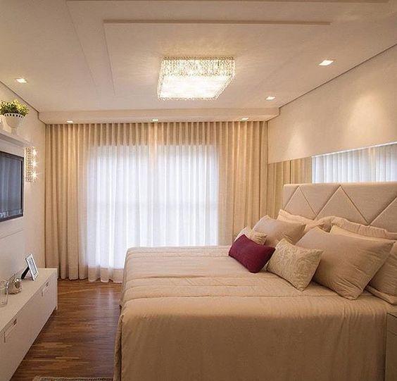 Decoração de quarto de casal com almofadas e cortina em tons pastéis.