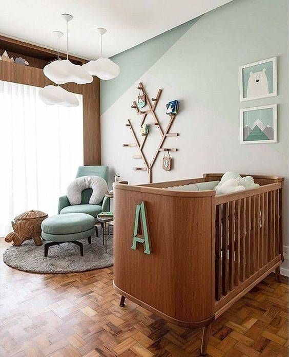Berço de madeira com a inicial do nome da criança e árvore na parede com ganchos.
