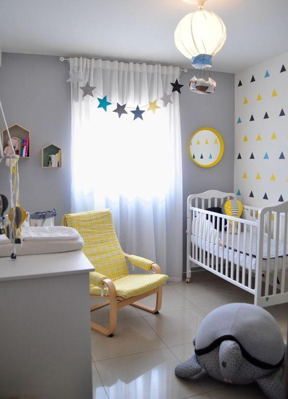 Lustre de balão e cadeira amarela de amamentação na decoração de quarto infantil.