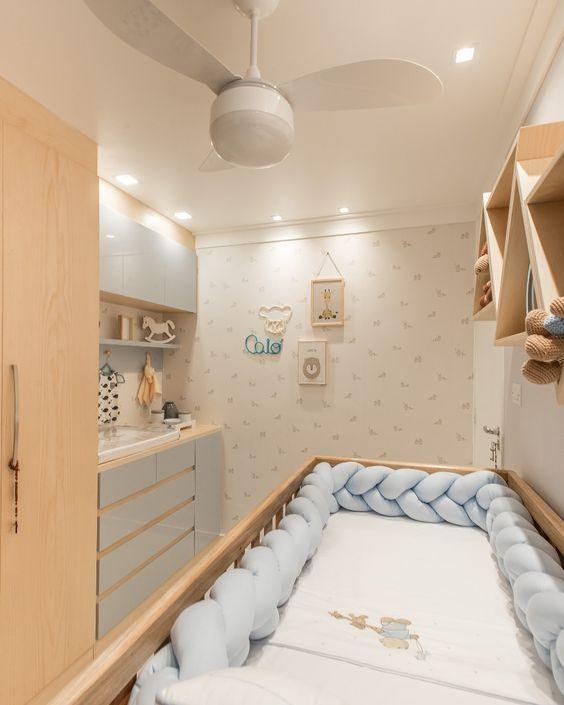 Quarto pequeno de bebê com berço, armário e trocador.
