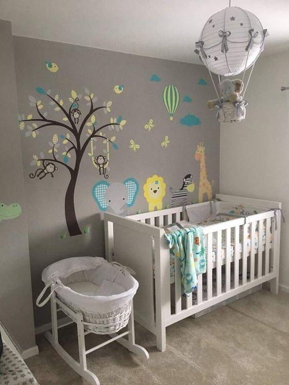 Papel de parede com árvore e animais em quarto de bebê.