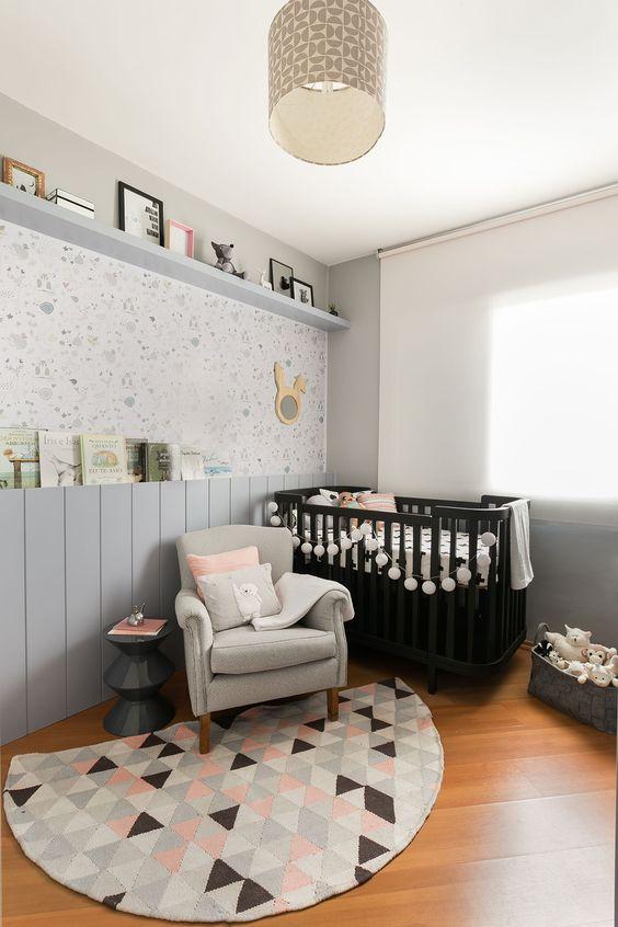 Quarto com berço preto, poltrona, prateleiras com itens decorativos e tapete com formas geométricas.