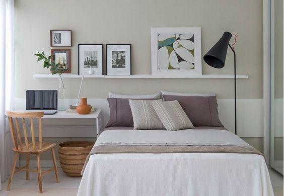 Quarto decorado com quadros e com mesinha para home office.