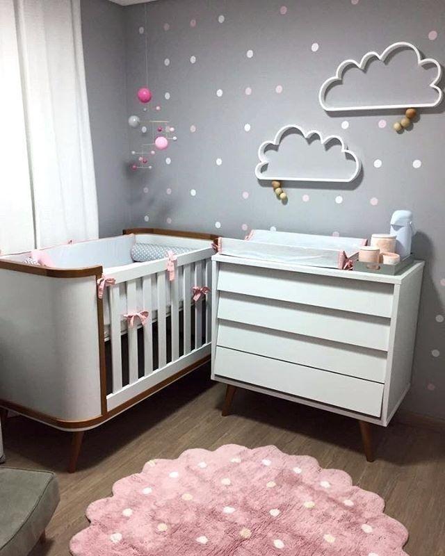 Decoração simples de quarto de bebê com tapete rosa e parede de bolinhas e nuvens.