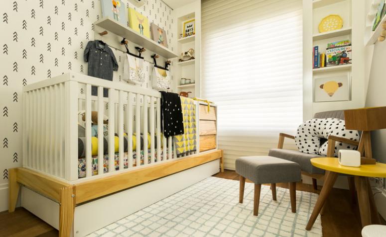 Decoração de quarto de bebê com berço, prateleiras e nichos nas cores amarelo, cinza e branco.