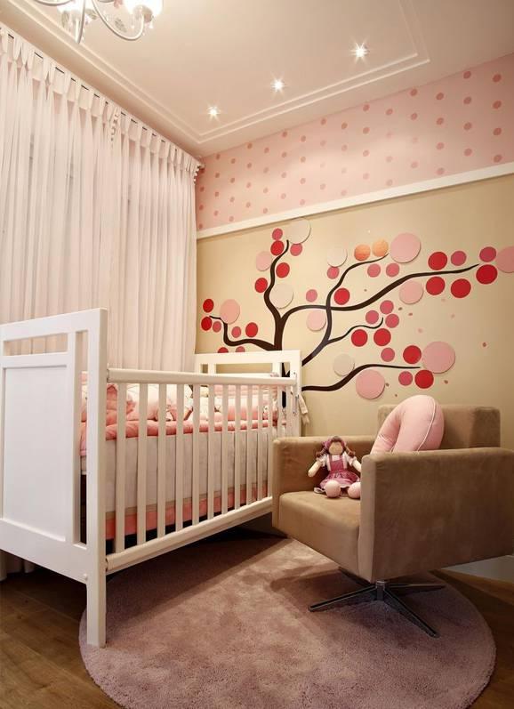 Quarto de bebê rosa com berço e poltrona para amamentação.