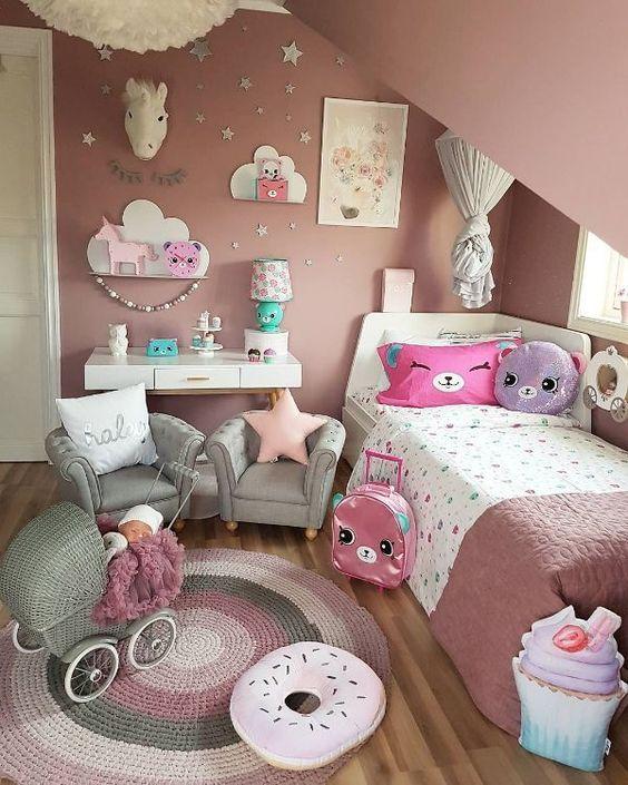 Decoração de quarto com almofadas coloridas, quadros e tapete.