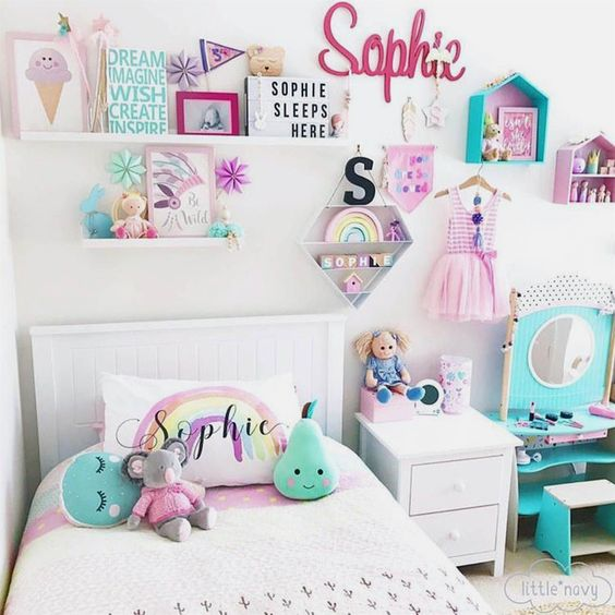 Decoração de quarto de menina com vários itens na parede, como prateleiras, quadros e nichos.