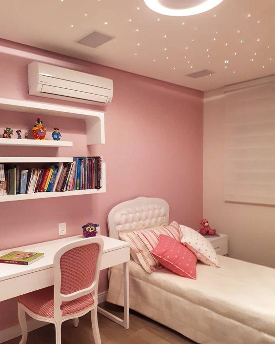 Quarto simples rosa com prateleiras, mesa de estudo e teto com pontos de luz.
