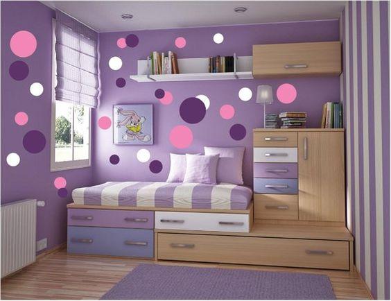 Quarto decorado nas cores branco, rosa e roxo com muitas gavetas.
