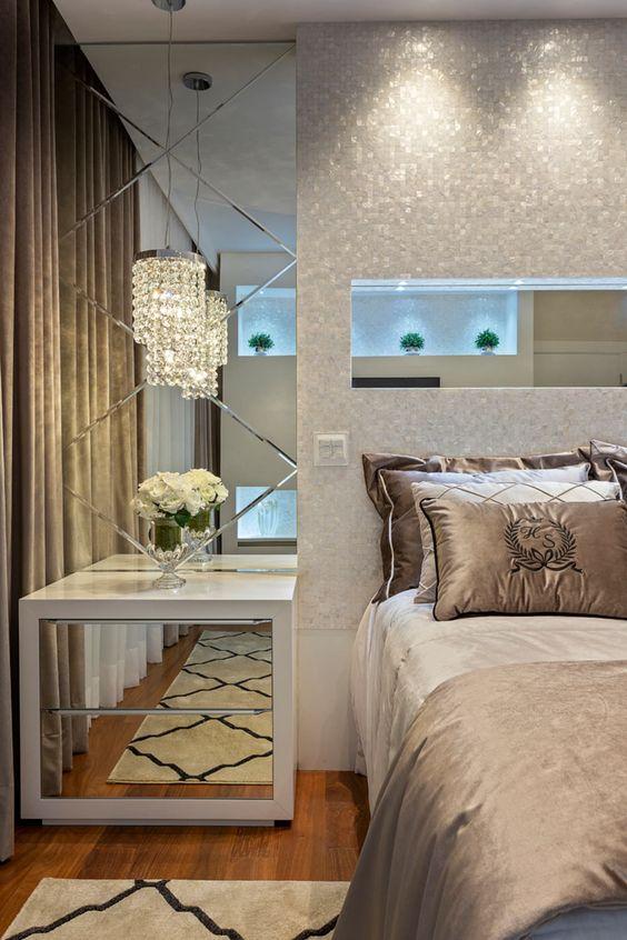 Lateral da cama espelhada com mesinha de cabeceira com gavetas também espelhadas.