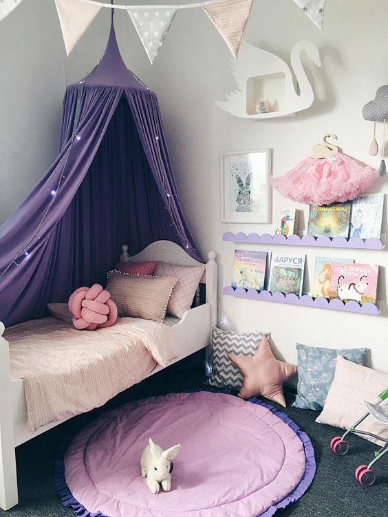 Decoração de quarto de menina com tenda em cima da cama.