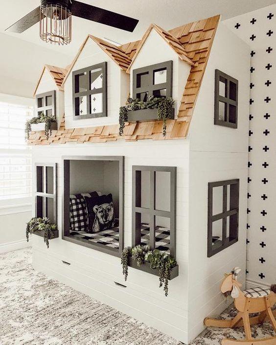 Cama dentro de uma estrutura que parece uma casa com janelas pretas e plantas suculentas.