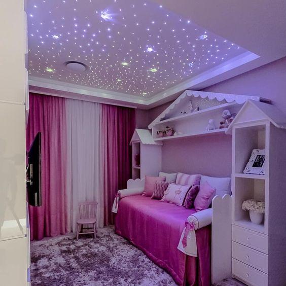 Quarto com cristeleiras que parecem casinhas e o teto com pequenos pontos de iluminação que parecem estrelas.